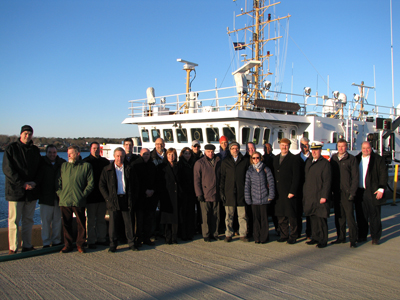 Group of people standing on a dock in front of a ship.